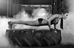 woman doing press ups on tire stock photo