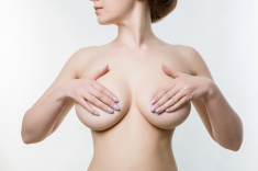 female breasts covered with hands, checking for breast disease, stock photo