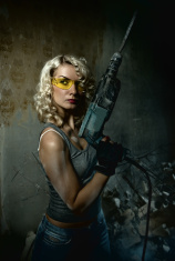 Beautiful blond woman with heavy drill in her hands stock photo